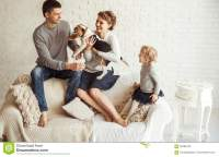 Portrait Of Happy Family With Pet Dog On Sofa In Living