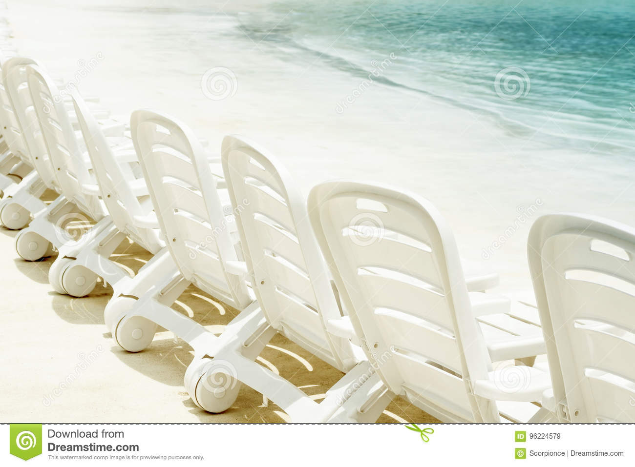 White Plastic Sun Loungers Row Of Plastic Sun Loungers By The Water On A White Sand Beach