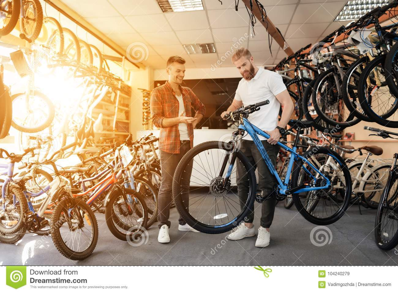 A Bike Store A Seller At A Bicycle Store Helps A Young Buyer Choose A New