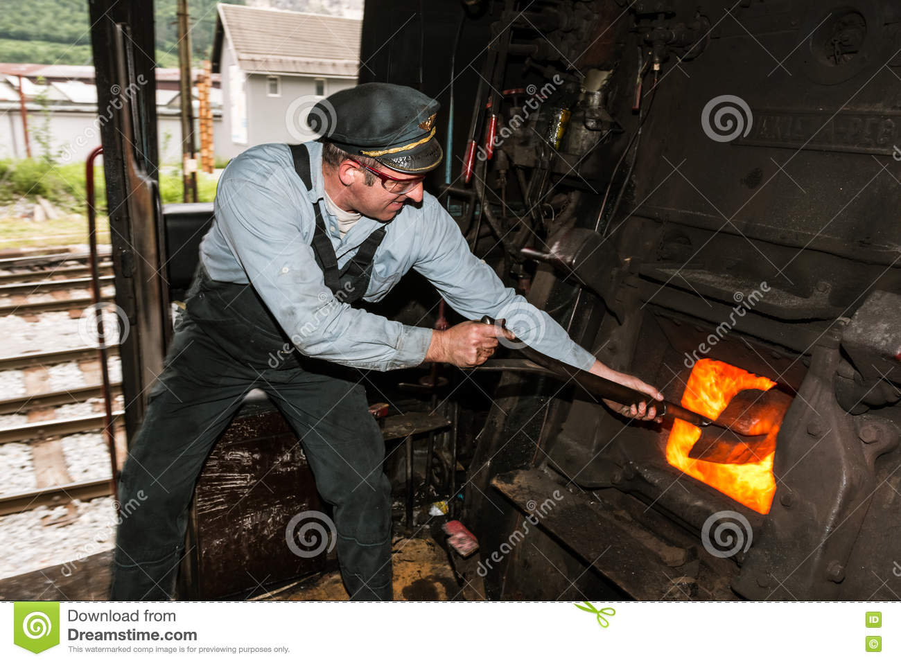 Sooty Stoker Shoveling Coal In The Furnace Of The Steam