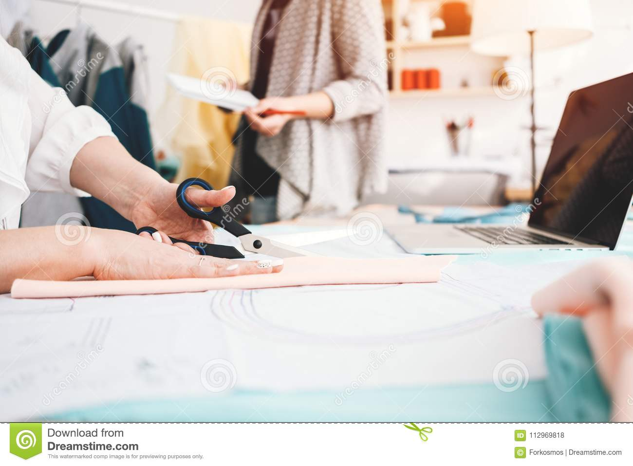 Bureau Designer Two Young Clothing Designer Working With Fabric And Laptop In