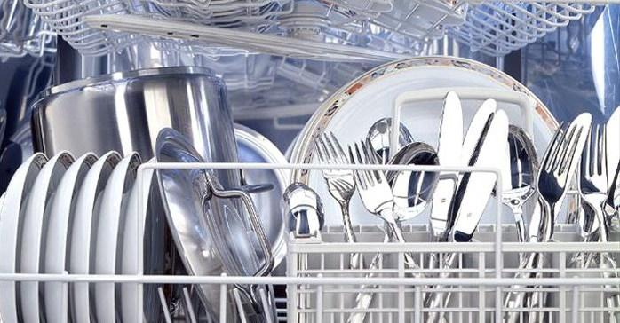 A dishwasher full of clean crockery & cutlery, from inside