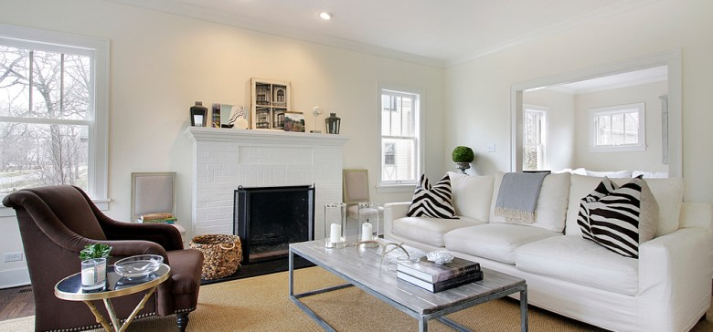 Clean white living room with view into family room