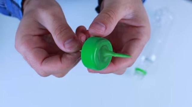 Heat bottle cap and press with toothpick to make nozzle