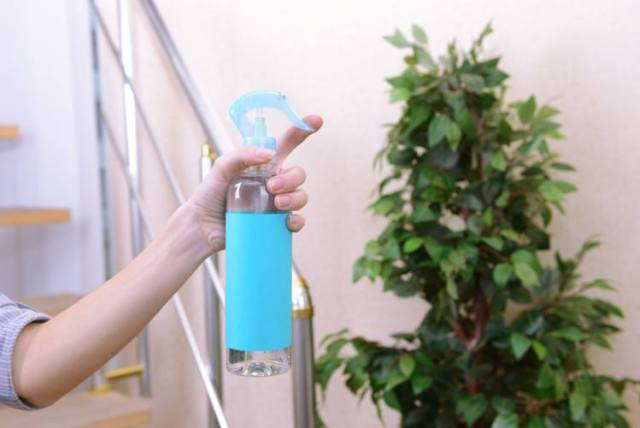 Sprayed air freshener in hand close-up