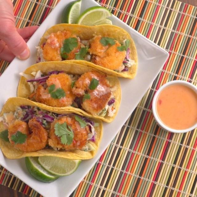 Placing three sweet chili shrimp tacos on corn tortillas