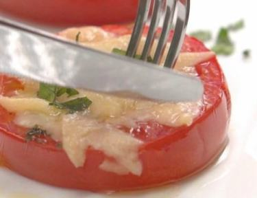 Close-up of eating Parmesan baked tomatoes with knife and fork