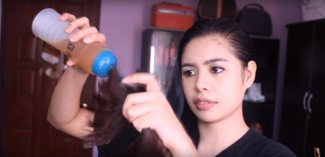 Applying oil mask to the ends of damaged hair.