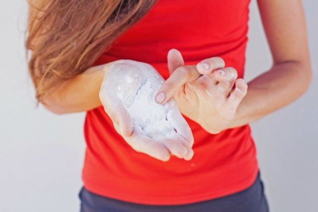 Woman holding dry shampoo powder in her hand
