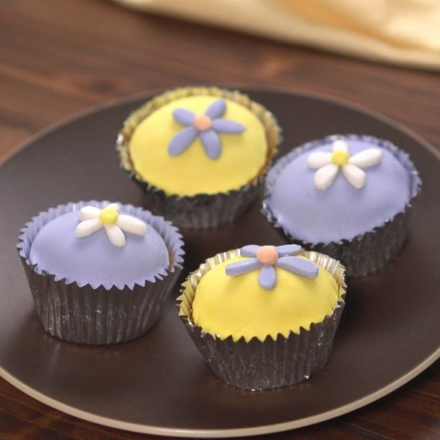 Four purple, white and yellow cupcakes decorated with marshmallow fondant flowers