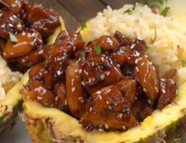 Close-up of teriyaki chicken pineapple boats on white plate