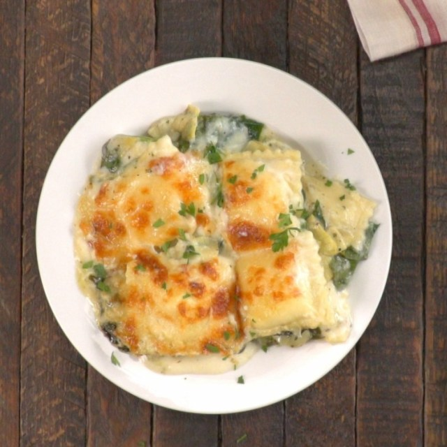 Creamy spinach and artichoke ravioli bake on a white plate