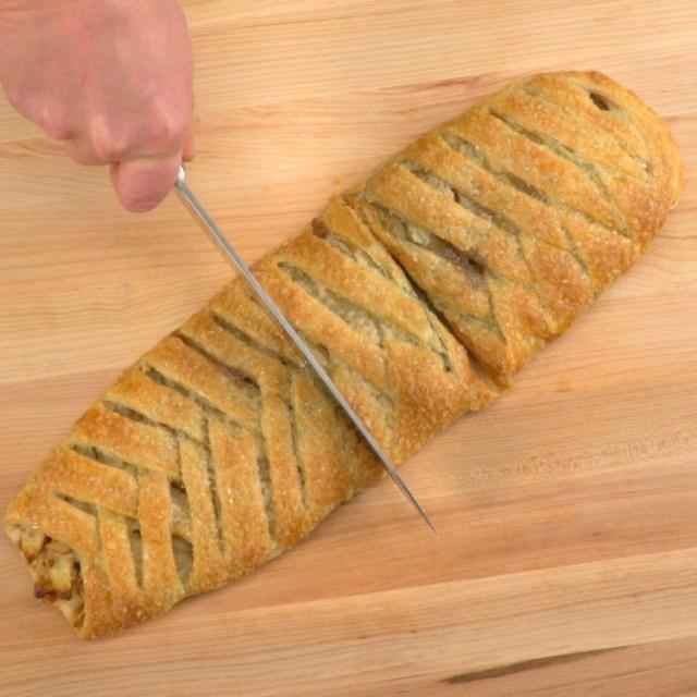 Cutting into braided apple walnut strudel to eat
