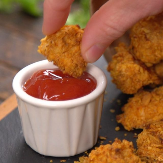 Dipping a piece of baked garlic popcorn chicken in ketchup to eat
