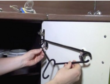 placing a hanger on metal hooks on an inside cabinet