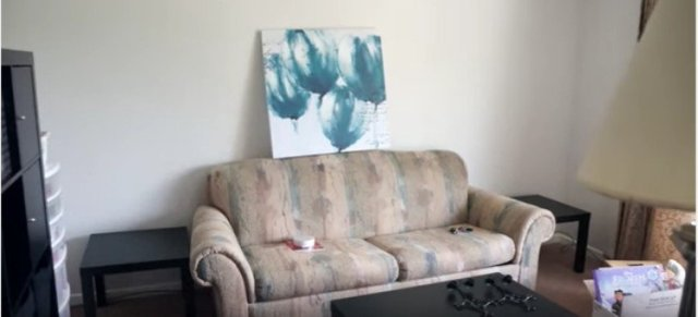 view of blue floral painting above couch