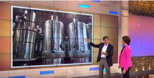Dr. Oz and woman stand in front of sugar processing slide