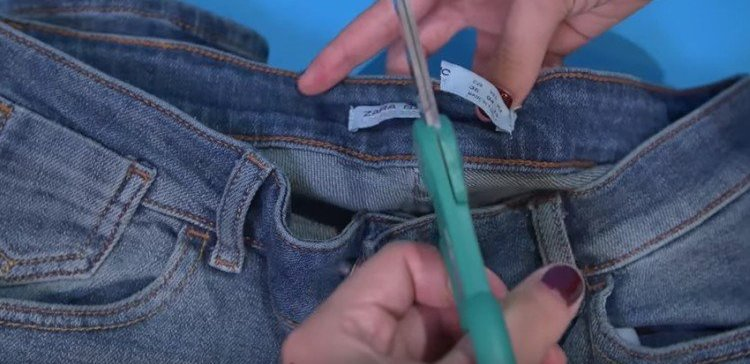 Image of woman cutting tag in jeans.
