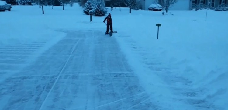 Guy uses hoverboard to clear snow away.