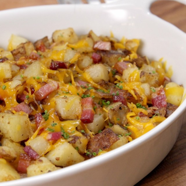 Bowl of potato hash loaded with cheese and bacon