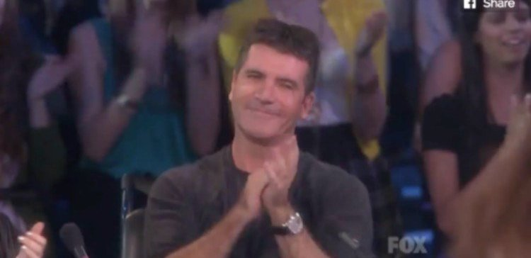 Simon Cowell claps in front of an audience
