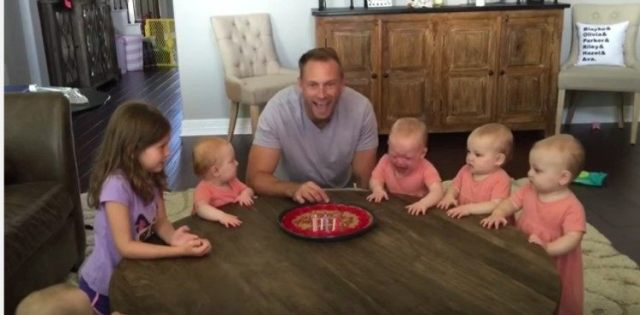 quintuplets baby crying by dad and sisters
