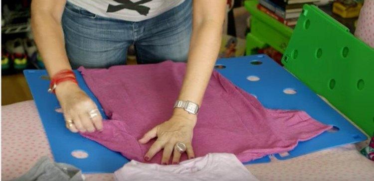 woman folding a pink t-shirt on a folding board