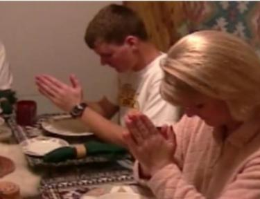 family bowing their heads in prayer at a table