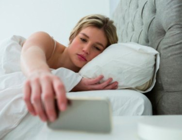 sleepy woman reaching for her phone in bed