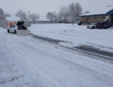 makeshift table snow plow attached to car on snowy road