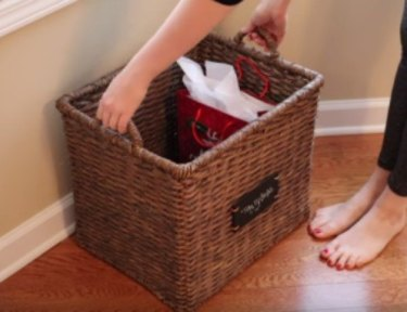 woman bends down to pick up a tidy-up basket