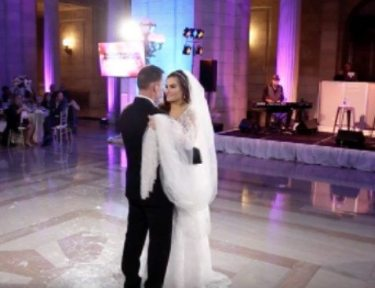 bride and groom dance in front of a live band