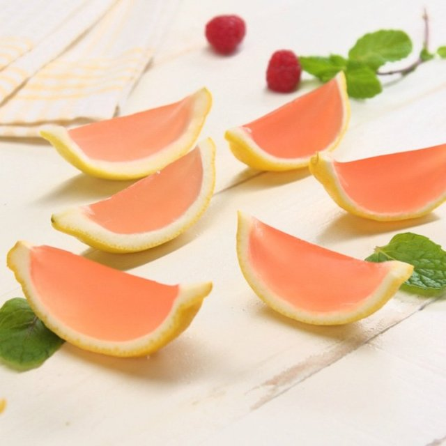 6 homemade pink lemonade Jell-O shots in lemon wedges