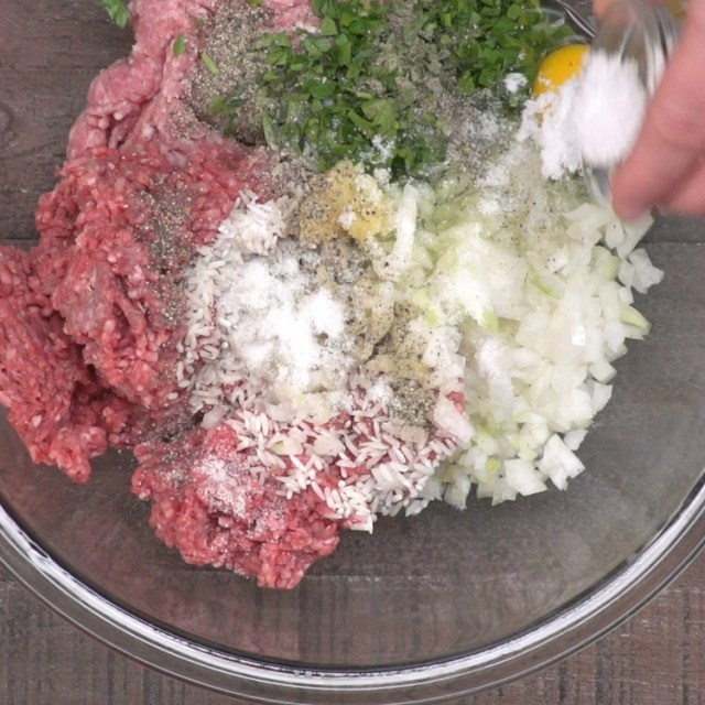 In a large bowl, combine ground beef, pork, onion, garlic, parsley, salt, pepper, egg and rinsed rice