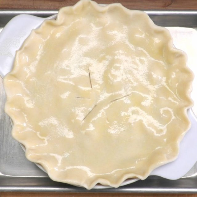 Brush the top of the crust with egg wash and place baking dish on a sheet pan
