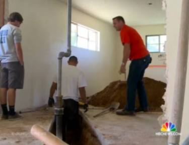 three contractors dig a hole in a home