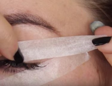 woman applying tape to eye area