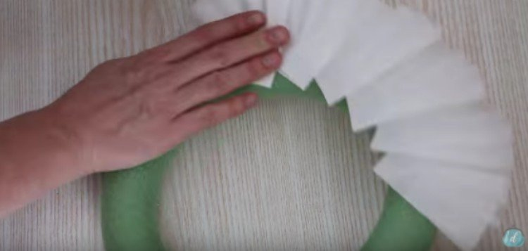 person adding coffee filters to wreath form