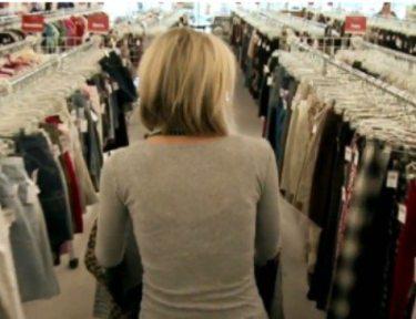 woman walking down a thrift shop aisle