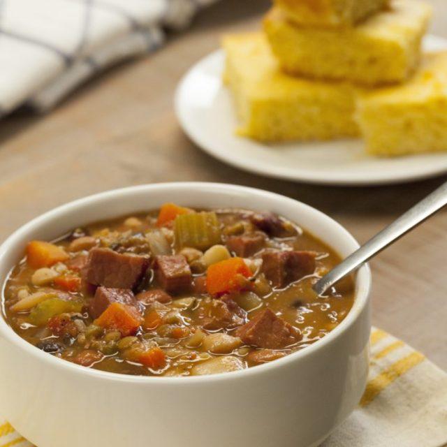 Slow Cooker Ham & Bean Soup bowl spoon in cornbread