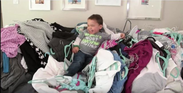 kid sitting on clothes