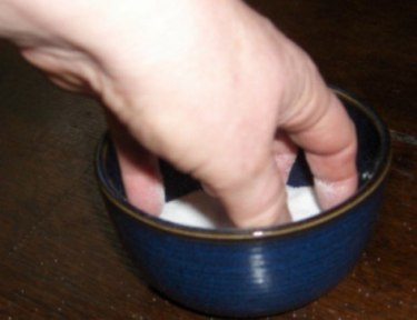 person retrieving salt from a small bowl