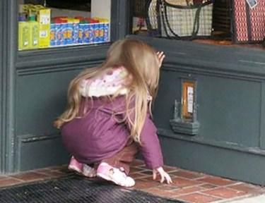 Little girl kneeling to look at fairy door