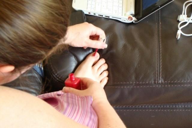 Painting nail on big toe with red nail polish