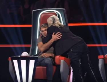 Image of Voice coach hugging another.