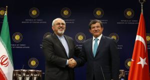 Iranian Foreign Minister Mohammad Javad Zarif (L) shakes hands with his Turkish counterpart Ahmet Davutoglu after a news conference in Ankara