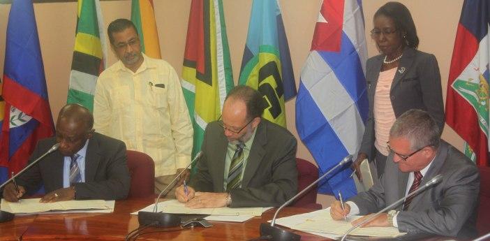 Signing the Agreement: (from left) Guyana's Minister of Foreign Affairs Mr. Carl Greenidge; CARICOM Secretary-General Ambassador Irwin LaRocque; Cuba's Ambassador to Guyana Mr. Julio Cesar Gonzalez Marchante