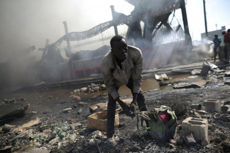 A man looks for goods amid the rubble outside of the Marche Hyppolite (Hyppolite Market), also known as Marche en Fer (Iron Market), after a fire that affected part of the market and the surrounding stands in Port-au-Prince, Haiti, February 13, 2018. (Photo via REUTERS/Andres Martinez Casares)