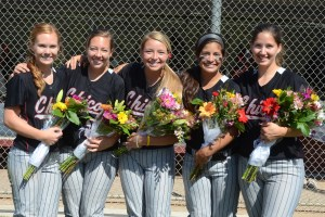 softball players smiling in a group, holding flowers for their senior celebration