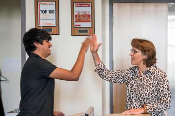 Admissions tour guide Hector Guzman (left) high-fives new President Gayle Hutchinson (right) who walks around campus to greet staff on her official first day of work on Tuesday, July 5, 2016 in Chico, Calif. (Jason Halley/University Photographer)